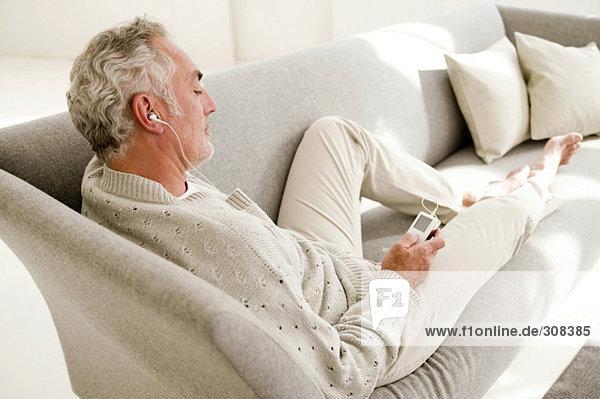 Erwachsener Mann hört MP3-Player  erhöhte Ansicht