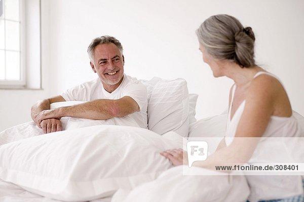 Erwachsenes Paar auf dem Bett sitzend  Mann lächelnd