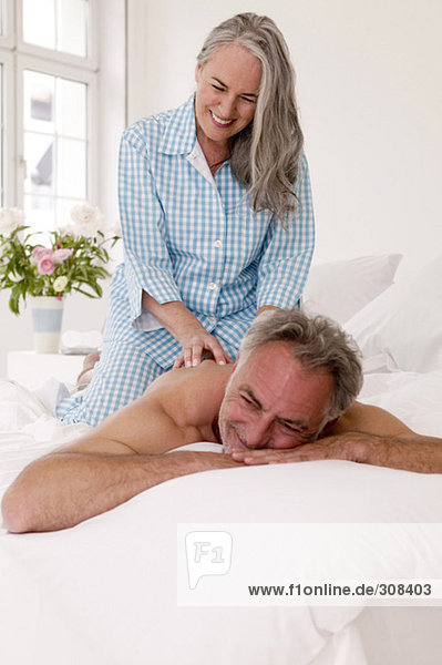Reifer Mann erhält Rückenmassage von einer Frau  lächelnd.