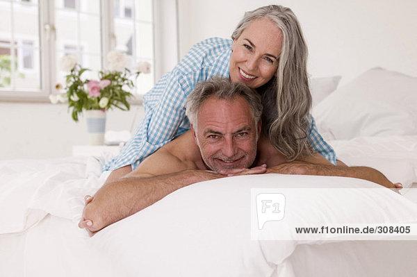 Reife Frau auf dem Rücken des Mannes auf dem Bett liegend  lächelnd  Porträt