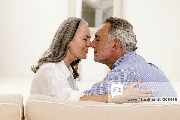 Reifendes Paar reibt die Nase zusammen  die Augen geschlossen.