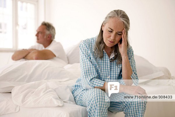 Mature couple sitting on bed (focus on woman in foreground with head in hands)