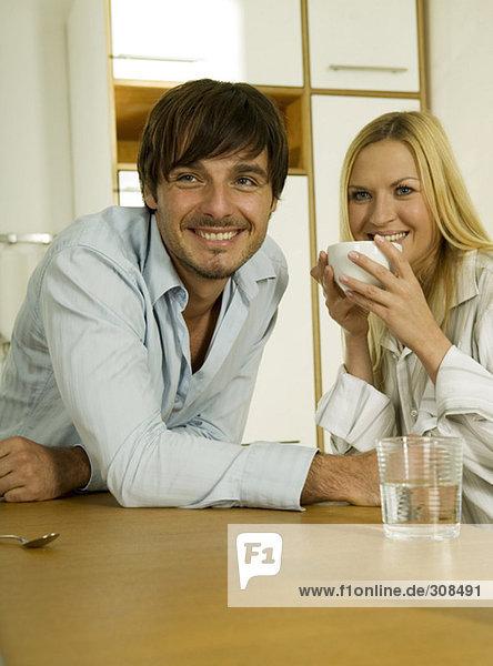 Junges Paar in der Küche  Frau hält Kaffeetasse  lächelt