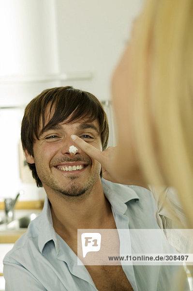 Junge Frau zeigt Nase des Mannes  Nahaufnahme