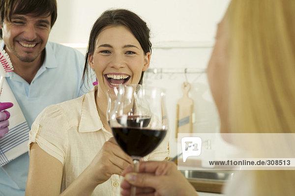 Drei junge Leute trinken Wein in der Küche  lächelnd  Nahaufnahme