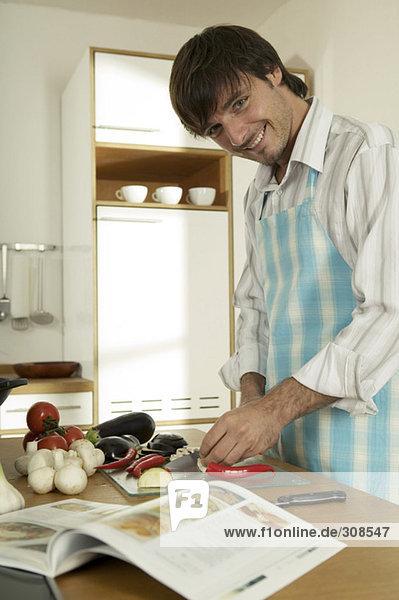 Junger Mann beim Schneiden von Gemüse in der Küche  Portrait  Nahaufnahme