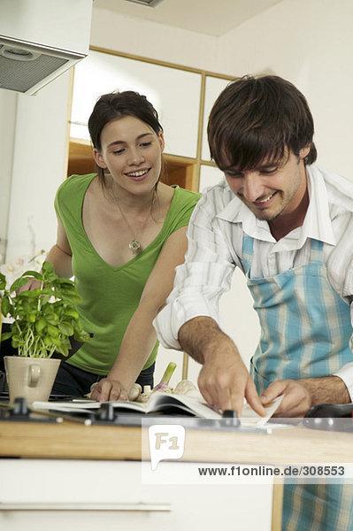 Junges Paar schaut sich das Rezeptbuch in der Küche an  lächelnd