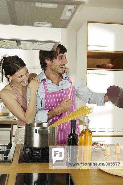Junges Paar kocht Spaghetti  schaut weg  lächelt