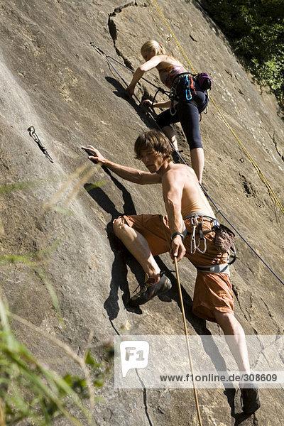 Junges Paar beim Klettern in der Kletterwand