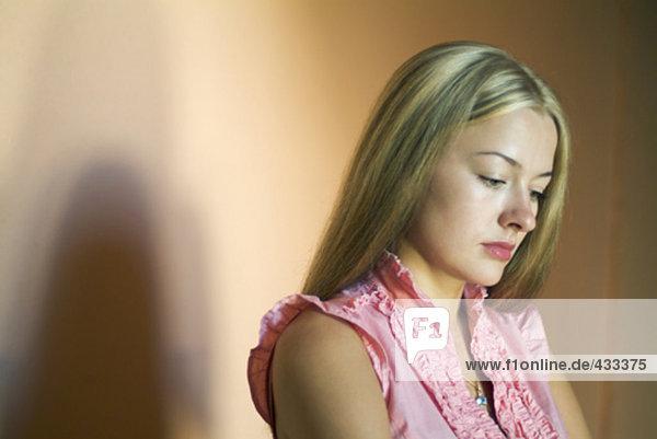 traurig aussehende Frau mit dunklen Schatten hinter ihr