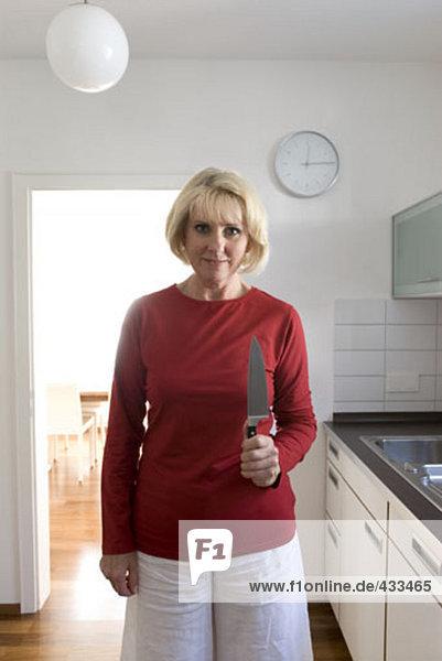 Reife Frau in Küche mit Messer in der hand