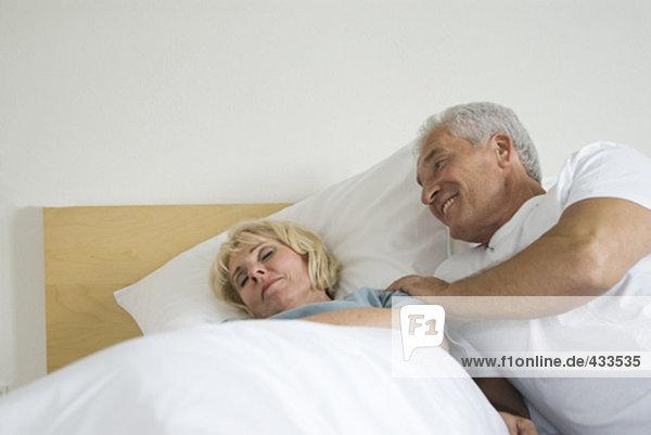 reifes Paar  Mann aufwachen seine schlafende Frau im Bett