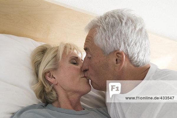 älterer Mann küssen Frau im Bett