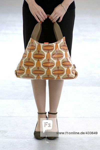 Detail of Frau hält bunten Handtasche