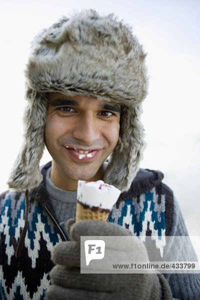 portrait of young man with fur hat and ice cream