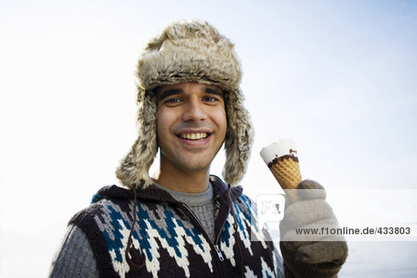 smiling man with fur hat having an ice cream outdoors in winter