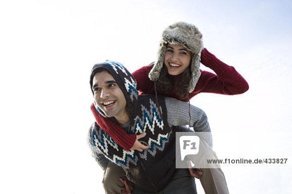 junge Frau mit Pelzmütze genießen piggyback ritt auf einem Land-Spaziergang