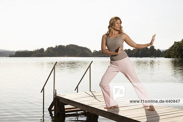 Frau beim Yoga am Steg