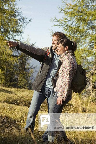 Ein junges Paar  das auf der Wiese spazieren geht  ein Mann  der darauf zeigt.