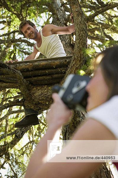 Junge Frau filmt Mann auf Baumhaus