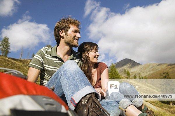 Junges Paar in den Bergen sitzend