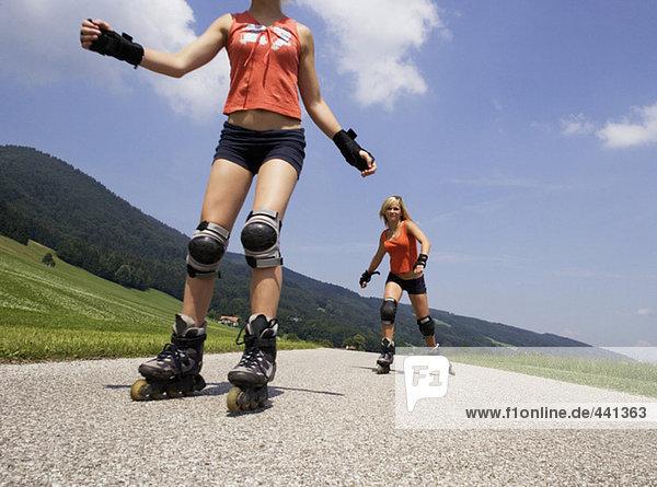 Zwei Teenager-Mädchen (13-15) beim Inline-Skaten Zwei Teenager-Mädchen (13-15) beim Inline-Skaten
