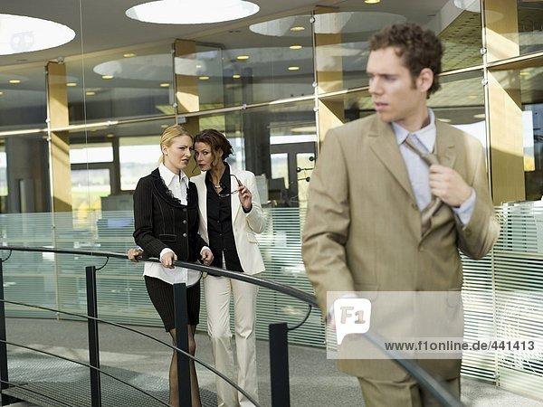 Frauen sprechen hinter dem Rücken eines jungen Geschäftsmannes