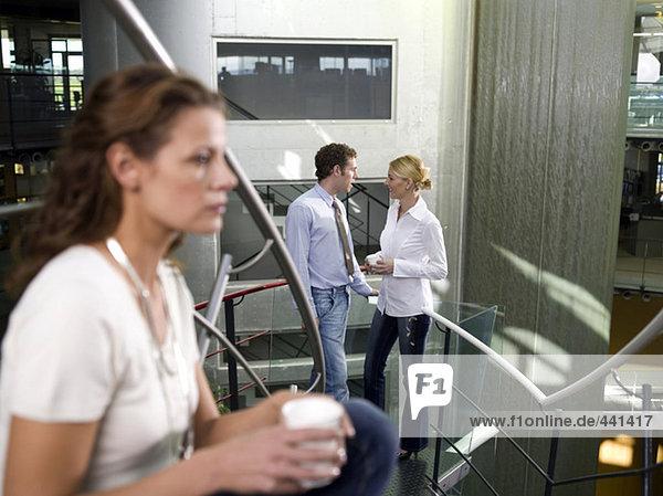 Junge Frau hört Kollegen beim Reden zu