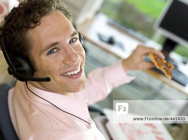 Junger Mann mit Pizza zum Mittagessen  lächelnd  Nahaufnahme  Porträt