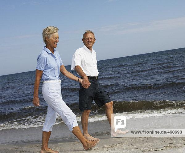 Paar Wandern am Strand.