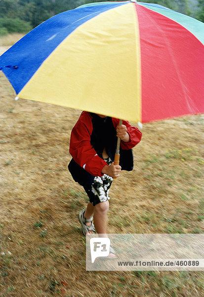 Ein Junge mit einem Regenschirm ausgeführt. Ein Junge mit einem Regenschirm ausgeführt.