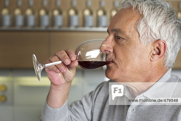 Gray-haired man with a glass of wine in his hand  close-up