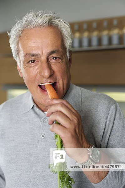 Gray-haired man eating a carrot  close-up  selective focus