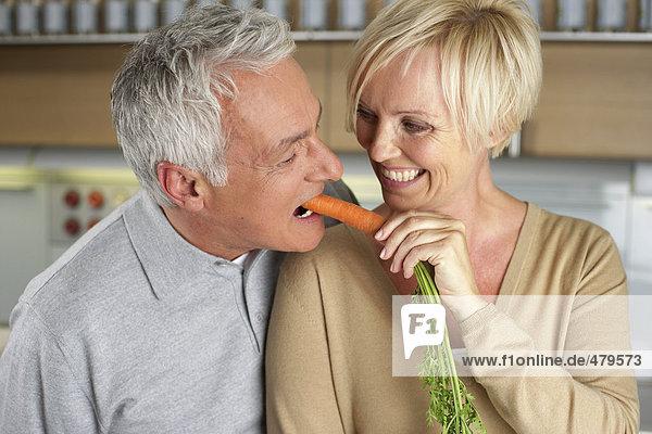 Blonde Frau füttert einen grauhaarigen Mann mit einer Karotte - Spaß - Liebe  fully_released