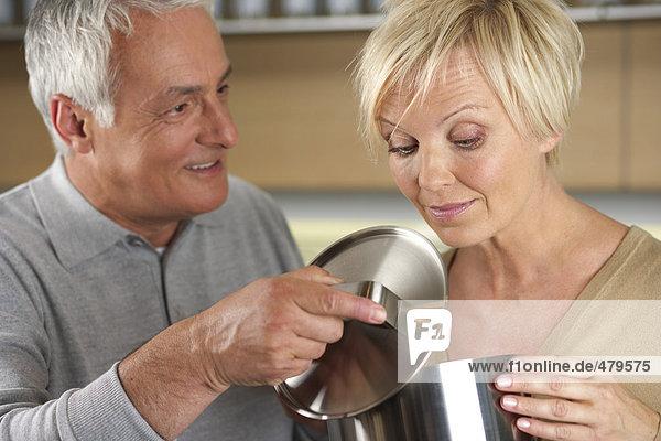 Grauhaariger Mann hält einer blonden Frau einen Kochtopf auf - Neugierde - Romantik,  fully_released