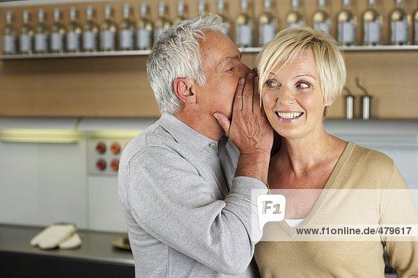 Grauhaariger Mann flüstert einer blonden Frau etwas ins Ohr - Geheimnis  fully_released