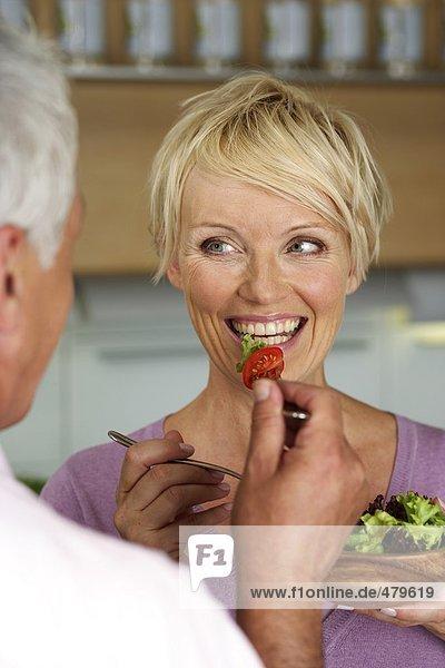 Blonde Frau mit einer Schüssel Salat in der Hand wird von einem Mann gefüttert - Ernährung - Gesundheit  fully_released