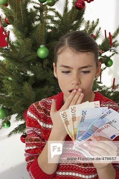 Surprised girl holding banknotes  Christmas tree in background
