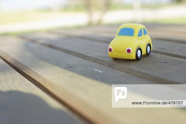 Kleines Spielzeugauto auf einem hölzernen Untergrund - Kindheit  fully_released