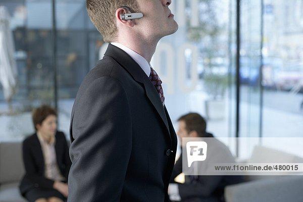 Ein Geschäftsmann mit Headset  im Hintergrund sitzen Geschäftsleute  fully_released