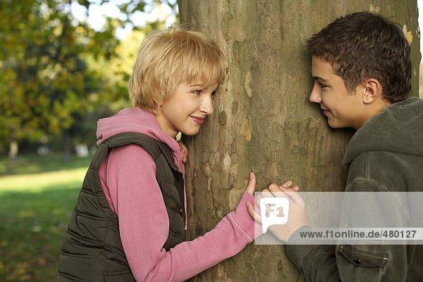 Jugendliches Paar neben einem Baum - Flirt- Romantik - Jugend  fully_released