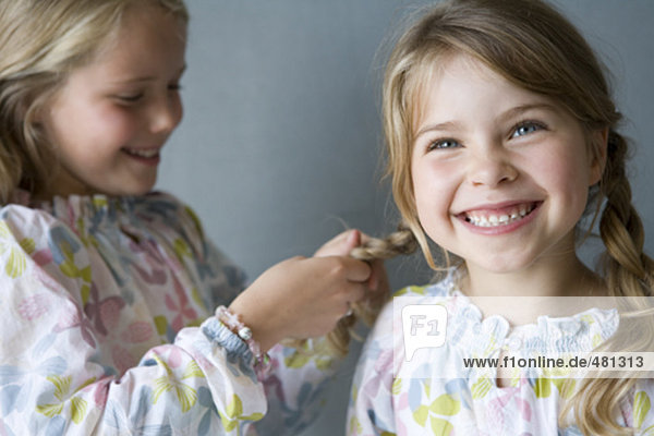 young girl smiling brightly while sister is making plaits in her hair