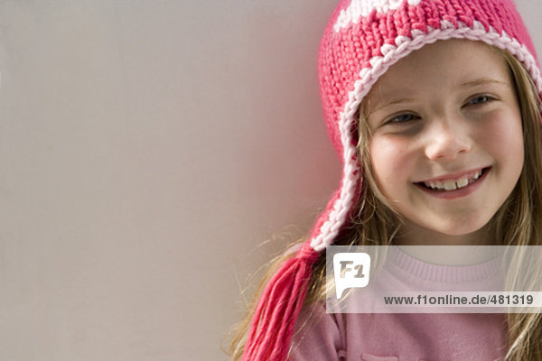 young girl with pink winter hats smiling contentedly