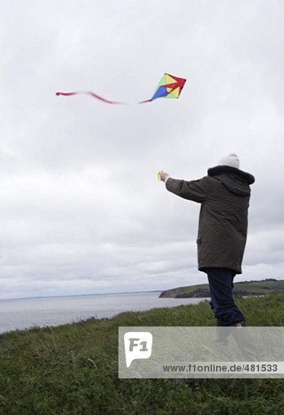 Mann Kite an windigen Küste im Herbst fliegen zu lassen Mann Kite an windigen Küste im Herbst fliegen zu lassen