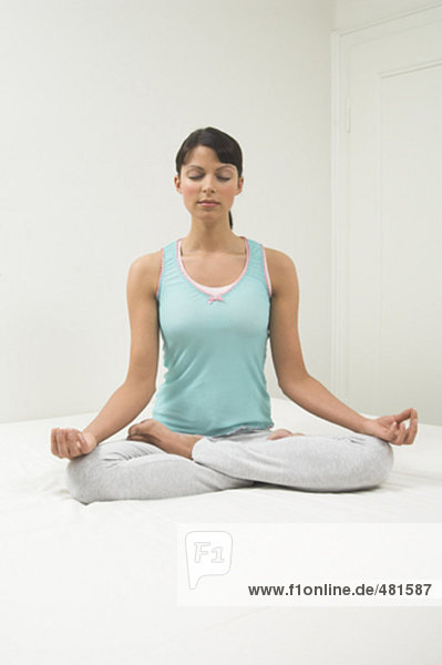 Portrait einer jungen Frau sitzen auf dem Bett tun Yog in Lotus-position