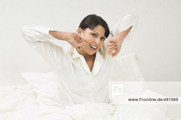 Frau in weißen Pyjamas in ihrem Bett am Morgen aufwachen