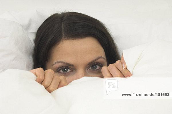 junge Frau im Bett hinter Duvet ausblenden