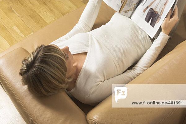 Vogelperspektive Blick auf junge Frau entspannenden auf Leather Sofa liest Magazin