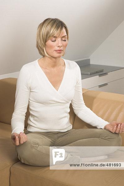 Portrait einer jungen Frau Meditation über Sofa im Wohnzimmer