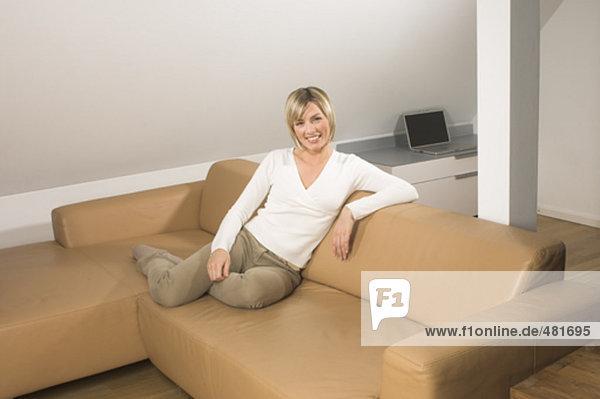 Ganzkörper Portrait lächelnd jungen Frau sitzen auf Leder-Sofa im Wohnzimmer